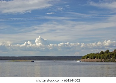 river on the background of blue sky, beautiful clouds in the summer, beautiful city view, a pleasure boat on the river under the summer blue sky