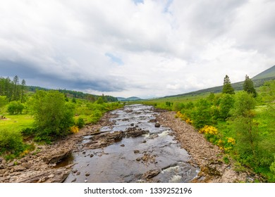 River Orchy in Scotland with green landscape in summer and clouds