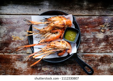 River prawns burned in a hot pan used as plate with wooden table in background at Amphawa Thailand