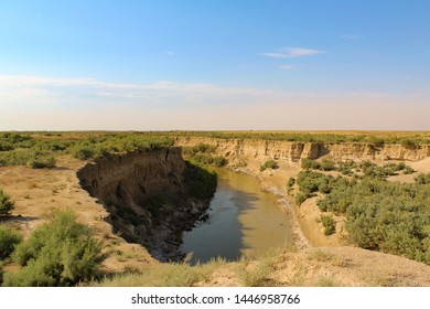River ravine in the steppe. A water is muddy. It's August and it's very hot.  Old bridge collapsed. There is no road through the ravine.  So, it should way back.