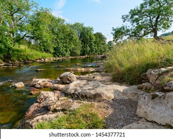 River Ribble flows between grass banks and over worn rocks near the village of Stainforth in the Yorkshire Dales