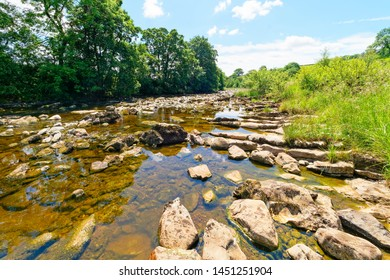 The River Ribble flows over and around rocks and boulders near the village of Stainforth in the Yorkshire Dales