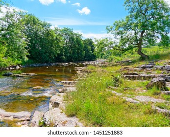The River Ribble winds its way through the Yorkshire Dales near the village of Stainforth on a bright summer day