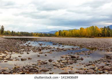 River rocks and color reflection on Flathead River, Montana in autumn with colorful fall trees in background