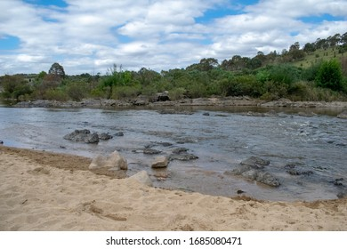 River with rocks in foreground and bushes and trees in background
