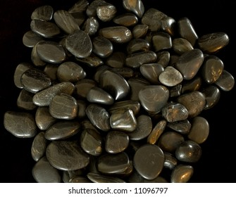 River rocks, polished by the water, are isolated against a black background