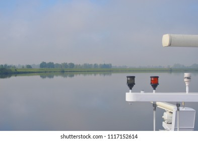 A river runs past parkland and trees, with a distant village. The pale blue sky with clouds is reflected in the still water, as is the riverbank. The boat's lights and navigation equipment is visible