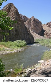 A river runs through a rocky, barren, desert landscape surrounded by thriving plant life in the western USA