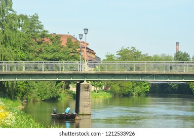 A river runs through a small village. Wildflowers and trees grow on the banks. A pedestrain bridge with lamps crosses the water, and a small boat is moored near one of the pylons. The sky is blue.