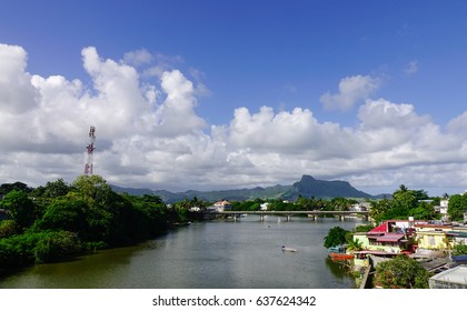 River scene with a small village on the bank in Mahebourg, Mauritius. Mahebourg is a small city on the south-eastern coast of Mauritius.