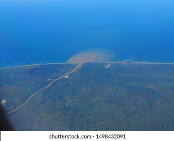 River sediment entering the sea. The brown soil and silt in the river is spreading out into the ocean in waves. Aerial view from plane.