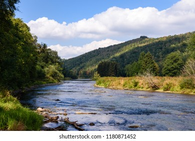River Semois with pine wood hills and nature in background near Vresse, Ardennes Region, Wallonia, Belgium.