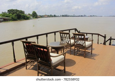River side restaurant seats tables near river for see river views Bangkok Thailand