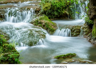 River with small cascades flowing in green forestin long exposure