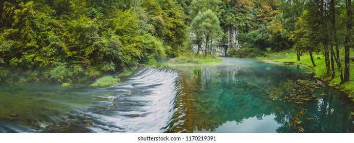River source panorama or spring of Krupa in Bela Krajina (White Carniola), Slovenia on misty cloudy day. Visible leaves and foggy green river with rock formation  and water flowing over dam - Shutterstock ID 1170219391