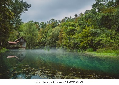 River source or spring of Krupa in Bela Krajina (White Carniola), Slovenia on a misty cloudy day. Reflection of wooden house, pier mill in foggy green river. Scary mystical water concept photo. - Shutterstock ID 1170219373