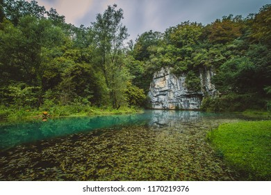 River source or spring of Krupa in Bela Krajina (White Carniola) in Slovenia on a misty cloudy day. Visible leaves and foggy green river with rock formation in the back. - Shutterstock ID 1170219376