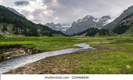 Ésera river in Spanish Pyrenees near Benasque. Water flows through flat, green meadows towards dark forest and sharp, rocky peaks in the background. Dense, grey clouds partially cover the mountains.