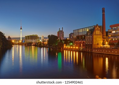 The River Spree in Berlin with some old industrial buildings and the Television Tower in the back at night