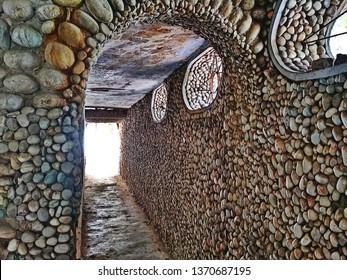 A river stone corridor in the underground meditation hall. Abandoned Maharishi Ashram in Rishikesh. Dungeon architecture.