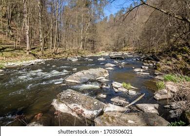 River with stones under blue sky in spring landscape. Oslava river, Czech Republic, Europe - Shutterstock ID 1703506021
