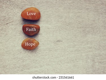 River stones with words written on them. love, taith and hope concept
