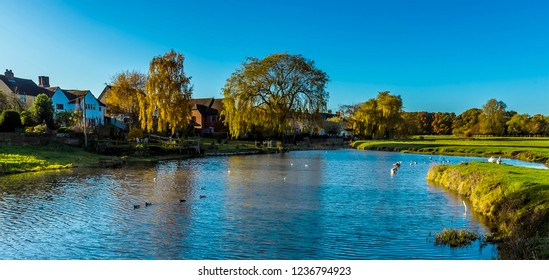 The River Stour winds past houses on the edge of Sudbury, Suffolk on a sunny autumn day