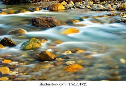 River stream water flow view. Water stnes in river stream. stream water motion