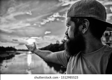 River sun reflection. Man in cap enjoy sunset while stand on bridge. Enjoy pleasant moment. Guy in front of blue sky at evening time admire landscape. Take moment to admire sunset nature beauty.
