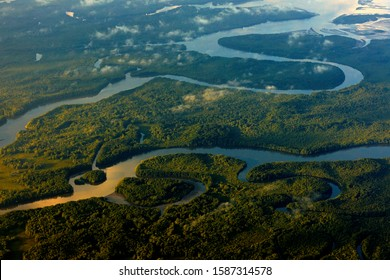 River sunrise in tropic Costa Rica, Corcovado NP. Lakes and rivers, view from airplane. Green grass in Central America. Trees with water in rainy season. Photo from air. Nature landscape near the sea.