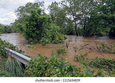 A river, swollen with muddy water after days of record ranfall, engulfs trees and overflows its banks onto the road on May 30, 2018 in Asheville, North Carolina