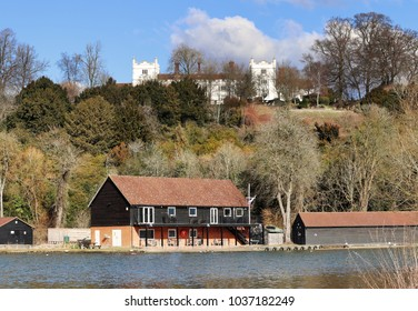 The River Thames in England with wooden boathouse and Danesfield House in the background