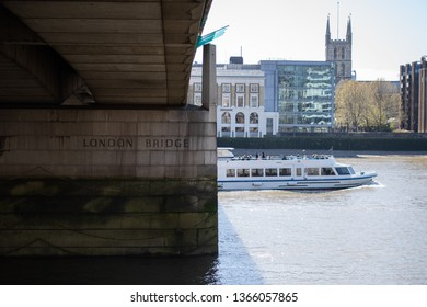 River Thames, London/UK - April 10 2019: London Bridge, with MY Sapele passing through. Church and offices in the background. London Bridge is engraved on the bridge pier.