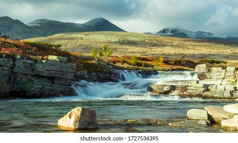 The river of Ula in Rondane, Norway during autumn. Vivid colors and soft golden light lights up the colorful scenery at evening. Snow capped mountains in the background. Holiday and travel concept.