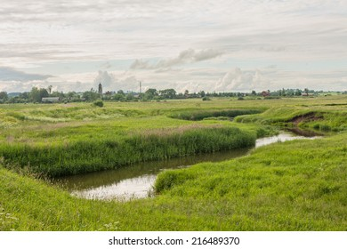 River valley with distant view on wooden village houses against cloudy sky background. Derevni, Yaroslavsky region, Russia.