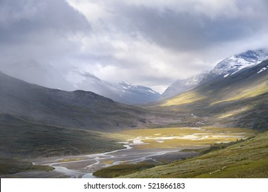 River valley lighted by golden sun light in autumn snow covered mountain landscape