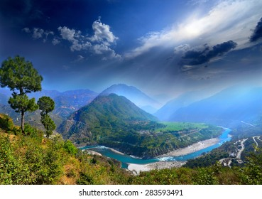 river and the valley to the village and fields on the background of blue mountain ranges of the Himalayas