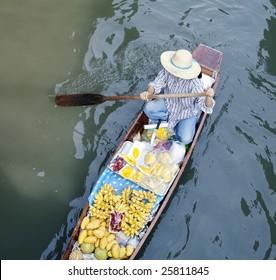 River vendor selling fruits at floating market in Bangkok