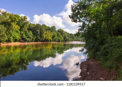 River view of Ocmolgee River in Macon Georgia with clouds reflecting off of water