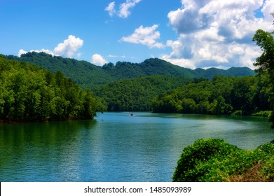 River view with two boats seen from a moving train traveling through the Nantahala National Forest