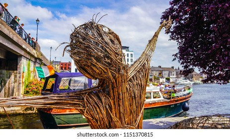 The river walk in Athlone Ireland along the river Shannon in june of 2018 with boat and straw figure.