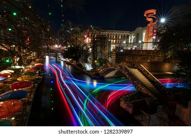 The River Walk in San Antonio, Texas is illuminated by colorful lights and animated by activity.