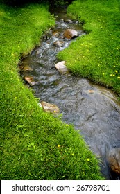 River water flowing past rocks and stones in green meadow