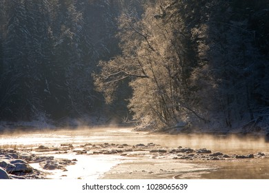 River water fog smoke with snow and ice and coast with stones and frost covered trees in cold freeze winter sunny bright morning light