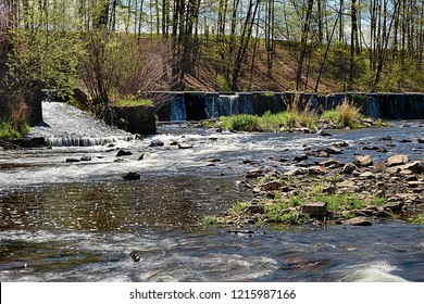 River with the weir runs over boulders