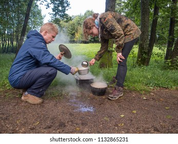 River Wieprza, Poland - August 23, 2017: Cooking a meal on a campfire in metal vessels during a  canoeing excursion on the Wieprza river