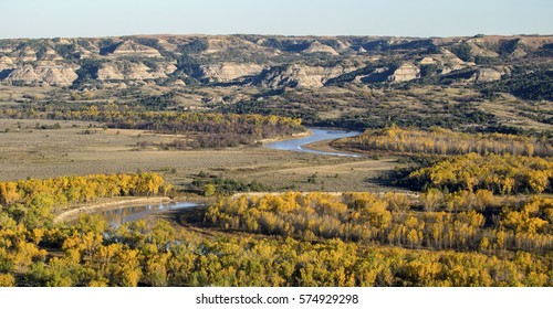 A river winds through fall-colored trees at Theodore Roosevelt National Park in North Dakota.