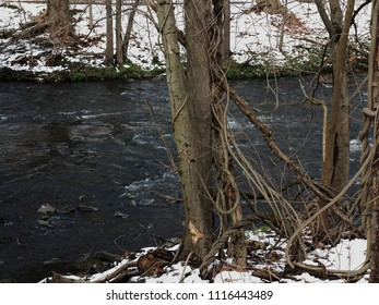 River in Winter - Flowing water in winter with snow on the banks.