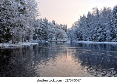 River in winter and tree branches covered with white frost