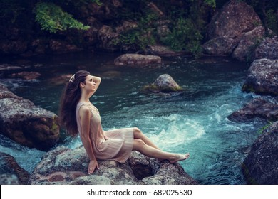 River witch, sitting on a rock in river. Pink dress, a fabulous image.Fashionable toning. Creative color.